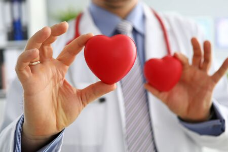GP showing two red hearts in camera close-up. Cardio therapeutist student education CPR life save GP make cardiac physical heart rate measure arrhythmia concept