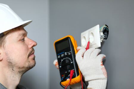 Electrician in helmet measures level electricity. Combined electrical measuring instrument, combining several functions. Handheld multimeter for basic measurements and troubleshooting at outlet Banque d'images