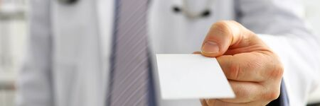 Male physician hand holding and giving white blank calling card closeup in office. Contact information exchange, introducing gesture at formal meeting personal or family doctor concept