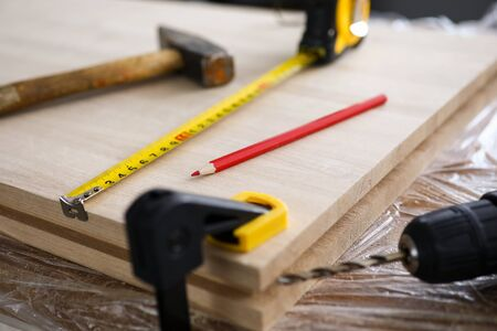 Carpenter tools and drill lie on wooden board. Production natural wood furniture. Environmentally friendly wood panels. Marking and installation wooden parts. Building parts by template