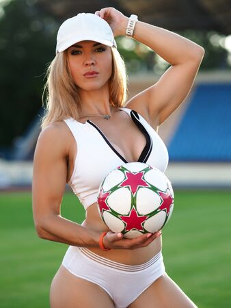 Beautiful girl stands on soccer field with ball. Training or competition for adults. Attractiveness womens football. Photo session at stadium, beautiful photo women for social network