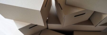 Pile of carton boxes standing in the middle of empty room in new house close-up