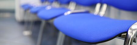 Line of empty blue visitor chairs at reception or in bank close-up