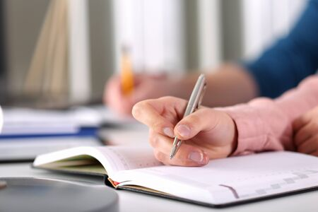 Close-up of businesswoman tender hand making notes in notebook. Manager writing financial statement on conversation. Business meeting and conference concept
