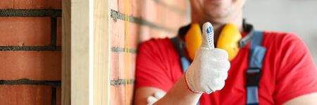 Close-up of happy male carpenter showing thumbs up. Smiling construction site worker working on project. Red brick wall. Renovation and professional builder concept Reklamní fotografie