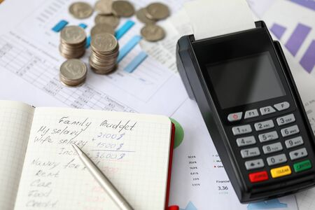 Close-up of paper and pen with family budget inscription and expenses. Detailed waste of money. Coins and terminal on desktop. Income and spending concept Stock Photo