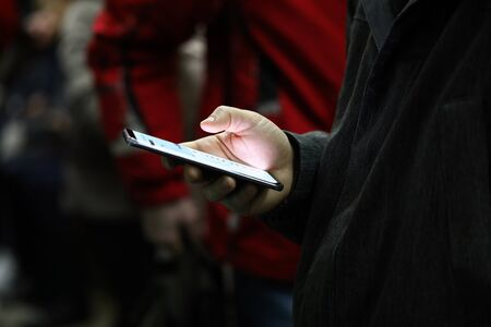 Close-up of persons hand holding mobile phone with light screen. Man scrolling news or playing game. Kill time and entertainment in public transport concept