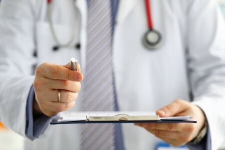 Hand of male GP passing to patient silver pen asking to sign some paper documents close-up Foto de archivo