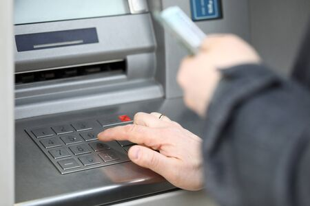 Close-up of man pressing pin code on cash machine outdoors. Person getting salary or pension. Credit card and atm. Money and financial stability concept Stockfoto