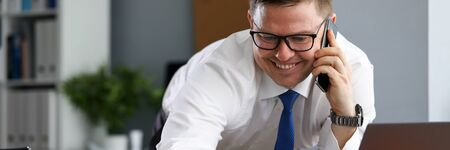 Joyful man in office speaks on phone near laptop. Introduction techniques to strengthen financial system company. Man works remotely from home during quarantine. Specialist with fresh look at work Reklamní fotografie