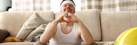 Guy sits at home carpet meditates and shows heart. Get out your usual comfort zone. Relaxing therapy improves your workout productivity. Cope with emotional pressure in stressful situations