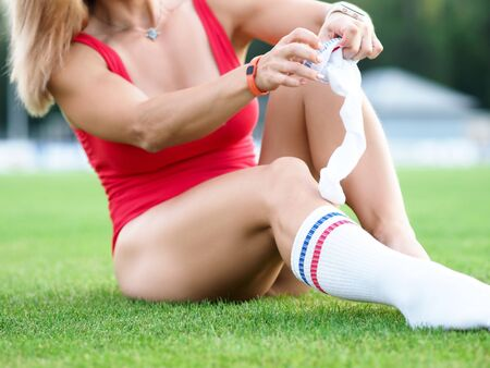 Girl sitting on grass stadium about clothes socks. Attendance womens match. Sportswear designed for fitness yoga gymnastics aerobics. T-shirt with wide straps perfectly supports chest