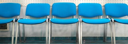 Close-up of empty blue chairs in row. Seat for person in waiting room or interview. Soft texture with metal legs. Comfort for body and simple design concept Фото со стока