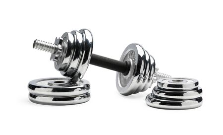 Silver coloured shiny metal dumbbell standing at pile of disks isolated over white background close-up Reklamní fotografie - 146384101