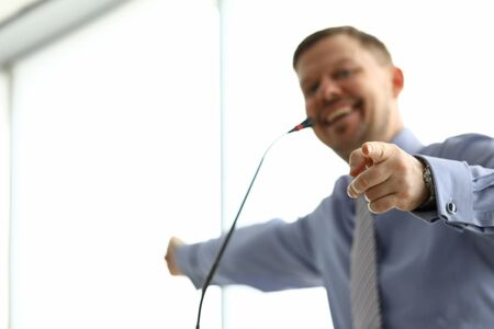 Smiling man points his finger towards microphone. At seminar or training speaker discusses material with all participants in event. Man turns to audience with questions, makes contact with audience
