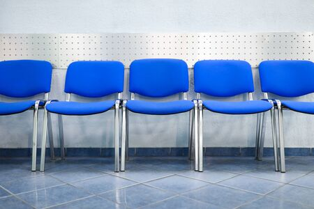 Line of empty blue visitor chairs standing near wall at reception or in bank close-up