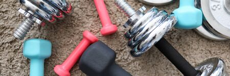 Equipment variety dumbbells are on carpet home. Regular exercise at home on self-isolation. Order sports equipment in online store. Wide selection dumbbells from variety materials Фото со стока