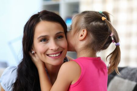 Portrait of smiling woman enjoying spending funny time with daughter. Little girl whispering secret in ear of happy mother. Childhood and family concept