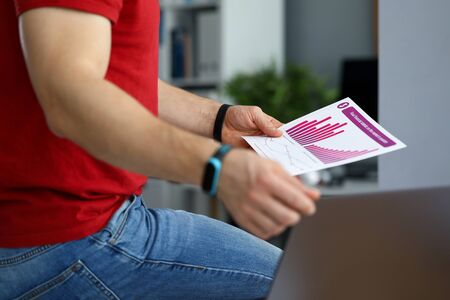 Guy in jeans analyzes financial report chart. Statistics for given scenarios lead generator. Business management. Customer loyalty information. Investment cost. Potential competitors