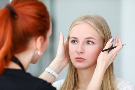 Makeup artist looks at symmetry models eyebrows. During healing process, loss color is minimal. Girl with master agree on shape, technique and shade eyebrows. Contour is filled with color Reklamní fotografie