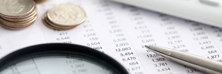Close-up of bank statement, calculator, stack of coins and pen. Bank employee making report. Statistics data. Financial bookkeeping and accounting concept