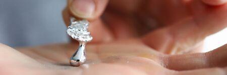 Male hand holding piece of liquid gallium close-up
