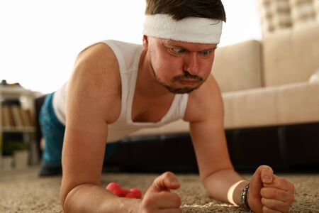 Portrait of middle aged man making funny face while training at home. Person in sportswear doing exercise on carpet. Indoors sport on quarantine and hobby concept Stok Fotoğraf