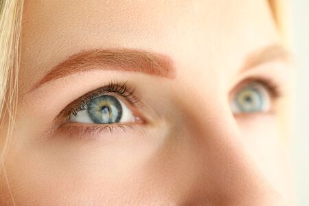 Close-up of young woman with perfect light brown eyebrow looking up. Macro shot of female after beauty facial procedure. Permanent makeup cosmetology and wellness concept Stock Photo