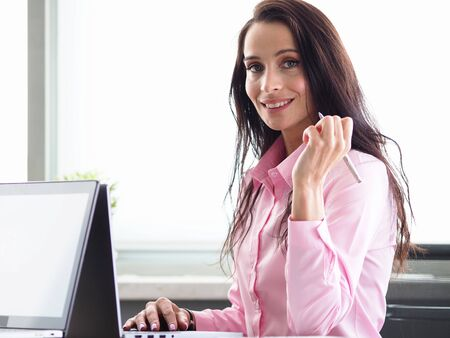 Portrait of smiling beautiful businesswoman looking at camera with happiness. Cheerful general manager signing documents. Woman at workplace in office. Business company concept Stock fotó