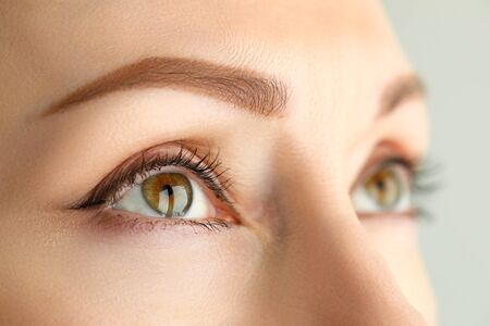 Close-up face model permanent makeup eyebrows. Girl is ready to transform her face. Natural eyebrows without obvious tattoo effect. Art procedure. Effect eyebrows tinted with shadows or pencil
