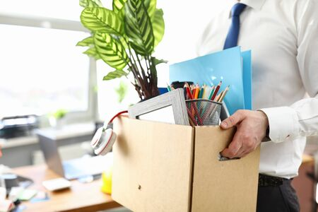 Businessman got fired during covid economy recession and taking his property out from office close-up Stock Photo