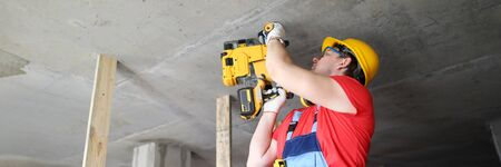 Builder works with special equipment on ceiling. Builder helmet holds heavy tool. Builder works puncher. Mounting guns for concrete are used by professional builders. Driving nails into hard surfaces