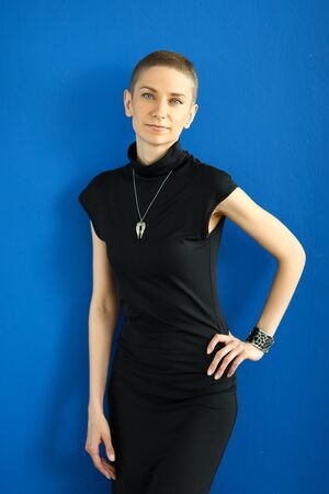Stylish girl in a black dress posing on a blue background. Creative model works with photographer Stock Photo