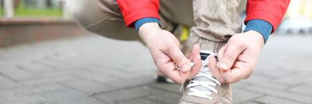 The man on the street leaned over to tie his shoe laces. Guy in the city straightens shoes