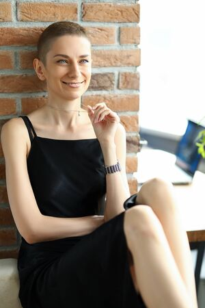 Fashionable girl in a satin black dress touches a chain on her neck. Stylish young woman sits on a brick wall background Stock Photo