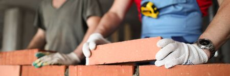 Close-up of builder laying brick with professional. Workmen at work, bricklayers building wall, contractor and worker. Masons using concrete and protective gloves