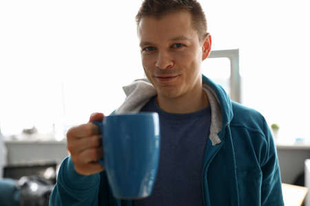 Guy in sportswear at home drinks from big cup. Man rejoices resting from work. Creative relaxation with cup coffee. Protein shake at home for athlete. Supporting healthy lifestyle in self-isolation Stock Photo