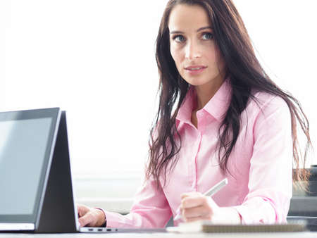 Portrait of cute businesslady looking away with seriousness and interest. Beautiful businesswoman working on laptop at workplace. Business and company concept