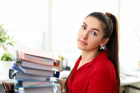 Portrait of tired businesslady working in office. Beautiful businesswoman holding big stack of paper folders and looking at camera with calmness. Business and company concept