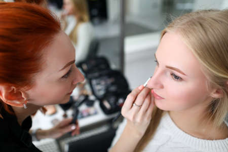 Portrait of professional makeup artist applying lipstick with special equipment. Young beautiful woman in beauty salon. Red-haired specialist holding palette with eyeshadows. Mua concept