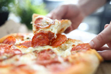 Male hand holding big piece of tasty fresh pizza close-up