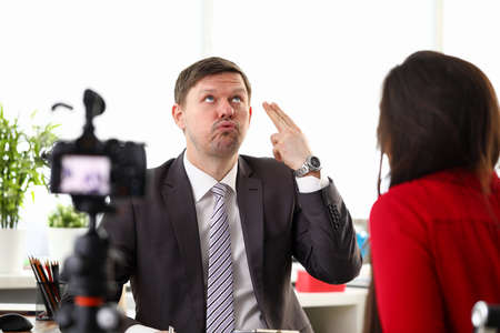 Portrait of businessman giving interview to journalist in office. Man in presentable suit with active expressions. Camera on tripod. Business appointment concept