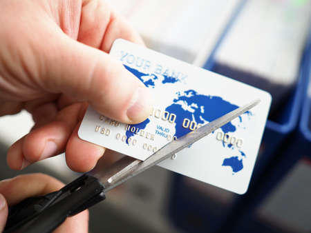 Male hand cutting banking card with scissors closeup