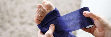 Close-up of male hands holding medical blue bandage and bandaging injured feet. Consequence of accident or sports trauma. Self help and sprain concept