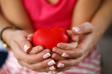 Focus on tender hands of caring woman holding baby palms and toy red heart. Loving relationship between mother and child. Family and motherhood concept