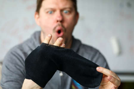 Man sitting at home surprised by big hole socks. Lack funds for purchase necessary things during economic crisis. Man put his fingers sock. Poverty against quarantine. Guy apartment in self-isolation