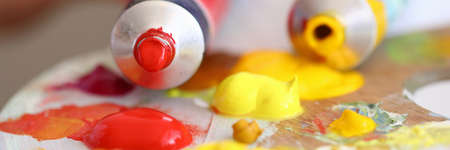 Close-up of tubes with red and yellow oil paints pouring on palette. Creamy texture. Tools for painting picture. Hobby and creative process. Art and artistry concept Stok Fotoğraf