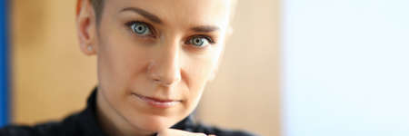 Close-up of lovely woman looking at camera with calmness and seriousness. Serious female person touching face by hand. Feminine with charming blue eyes