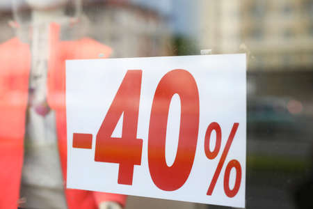 Close-up of sign with 40 percent announcement, shopping on reduced prices. Label of shop, announcement of discount or clearance. Selloff for clients, sellout reduction