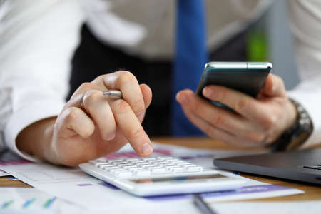 Close-up of hands of businessman using smartphone and calculator to count financial details. Man at workplace with phone, documents and pen. Banking and economy